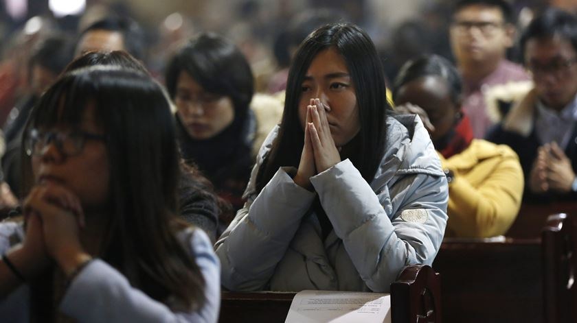 Católicos chineses rezam. Foto: EPA
