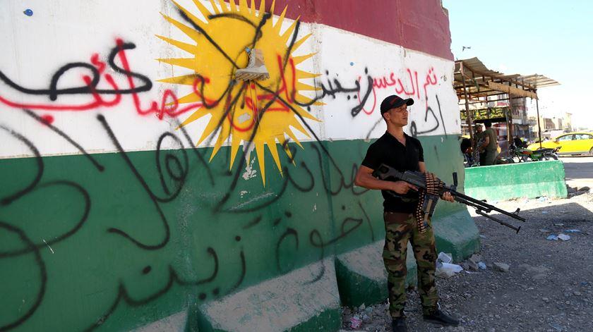 Miliciano xiita leal a Bagdad em Kirkuk frente a um mural com uma bandeira do Curdistão vandalizado. Foto: Barreq al-Samarrai/EPA