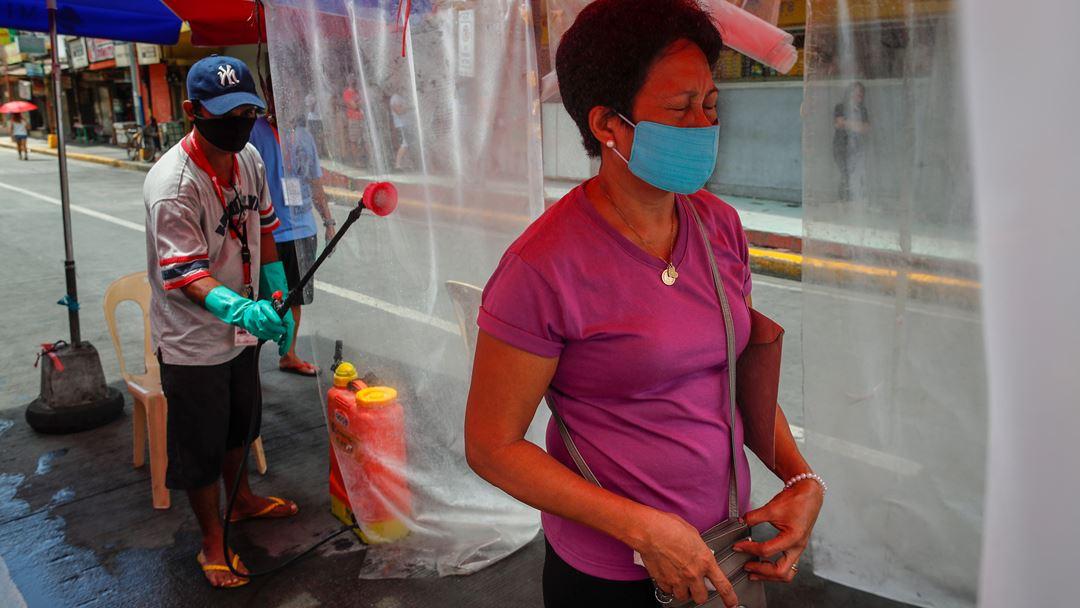 Manila, Filipinas. Uma mulher é pulverizada com desinfetante, à entrada de um mercado público. Foto: Mark R. Cristino/EPA