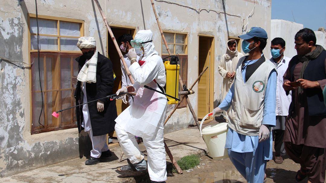 Helmand, Afeganistão. Profissionais de saúde afegãos desinfetam locais públicos na cidade de Helmand. Foto: Watan Yar/EPA