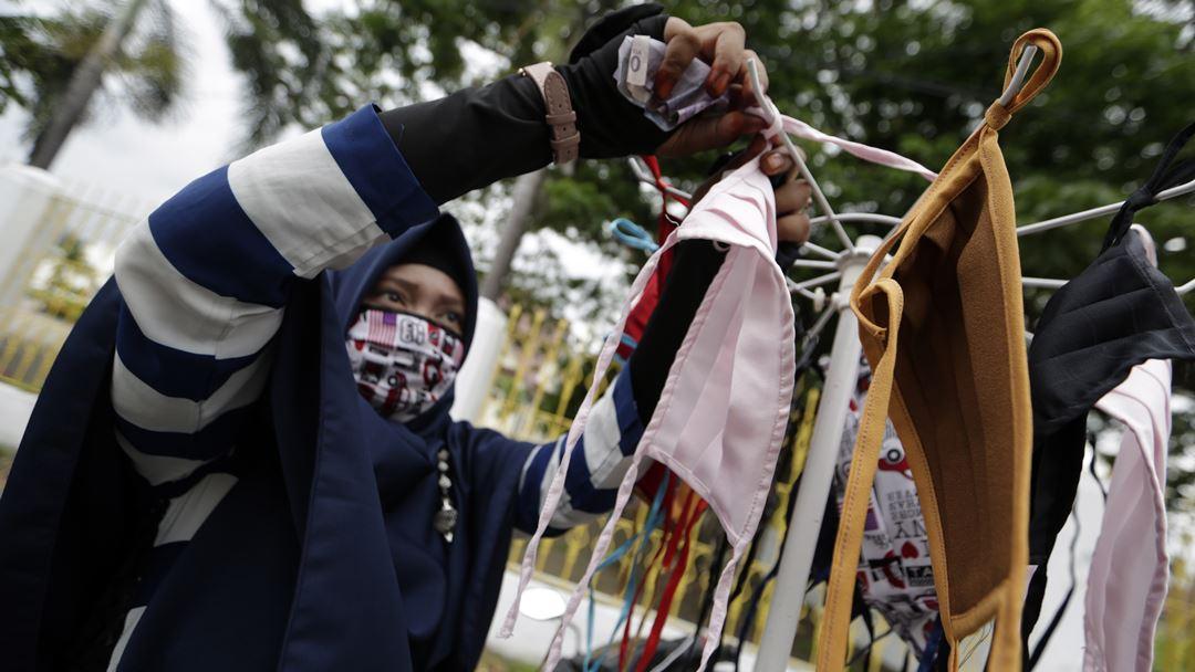 Banda Aceh, Indonésia. Mulher vende máscaras feitas à mão, nas ruas de Banda Aceh. Foto: Hotli Simanjuntak/EPA