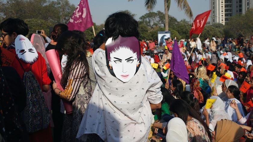 """Mulheres usam máscaras com o rosto de Qandeel Baloch, uma modelo e celebridade do Paquistão, assassinada pelo irmão porque """"desonrava"""" a família por se expor nas redes sociais. Karachi, Paquistão. Foto: Akhtar Soomro/Reuters"""