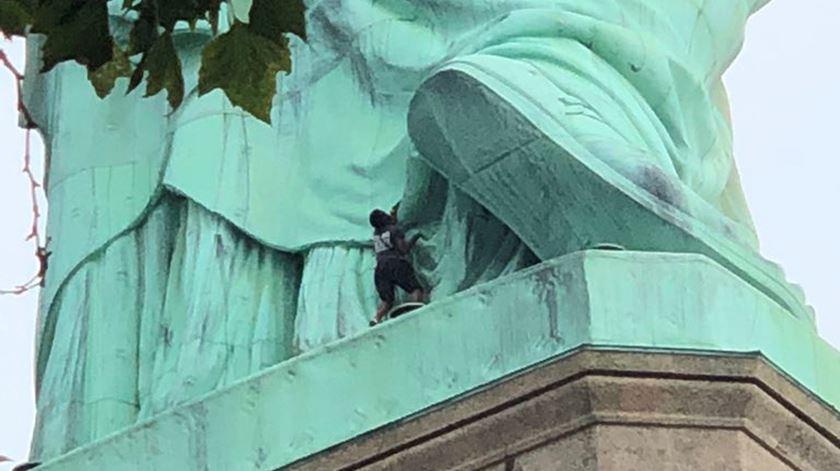 Mulher escala base da estátua da Liberdade em protesto
