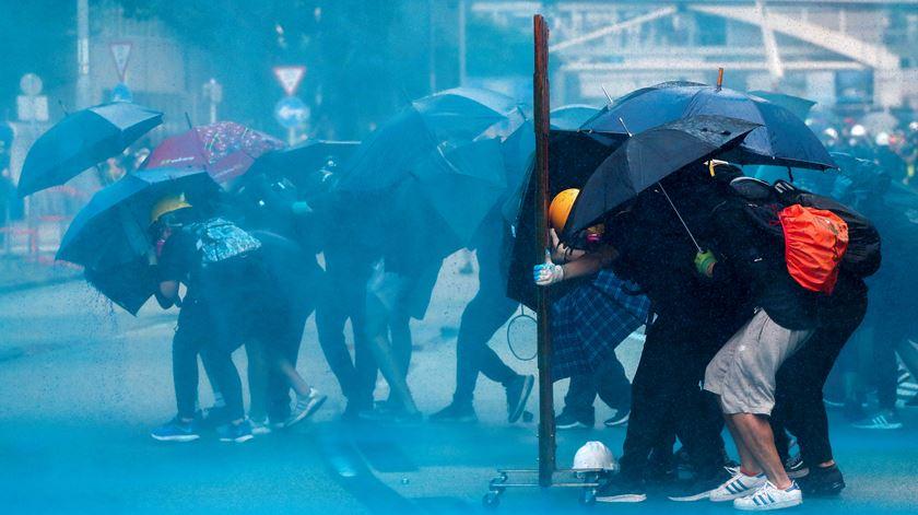 Manifestantes protegem-se dos canhões de água da polícia. Foto: Athit Perawongmetha/Reuters