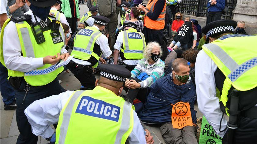 Ativistas ambientais colam partes do corpo ao chão junto ao Parlamento britânico