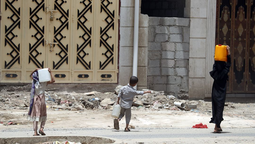 Sanaa, Iémen. Uma família transporta garrafões de água, depois de os abastecer numa fonte de água potável, montada por grupos de ajuda humanitária, para evitar o contágio entre a população do país em guerra. Foto: Yahya Arhab/EPA
