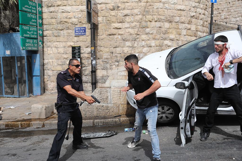 Polícia protege israelita que conduziu contra um grupo de palestinianos. Foto: Abir Sultan/EPA