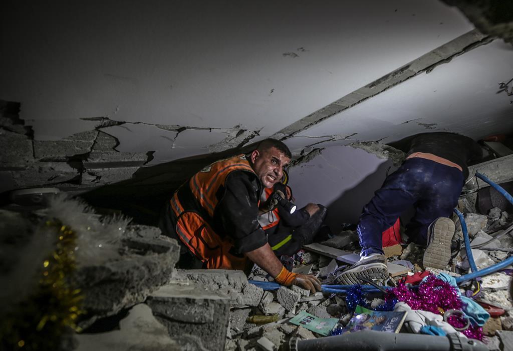 Elementos da Proteção Civil da Palestina procuram pessoas entre os escombros de um prédio destruído por Israel, em Gaza. Foto: Mohammed Saber/EPA