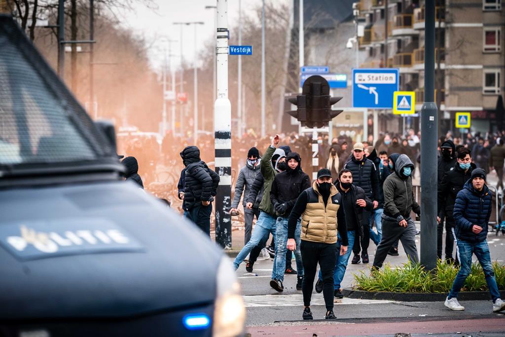 Manifestantes em distúrbias contra confinamento decretado, em Eindhoven, Países Baixos. Foto: Rob Engelaar/EPA