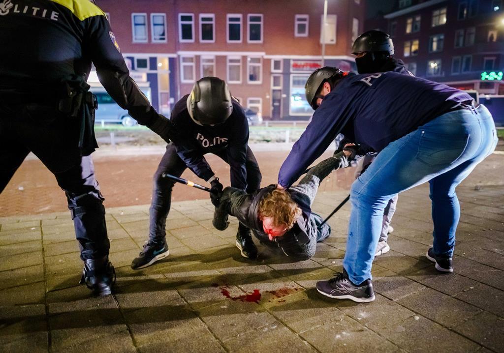 Homem é detido pela polícia, em Roterdão, nos Países Baixos, durante distúrbios contra confinamento. Foto: Marco de Swart/EPA