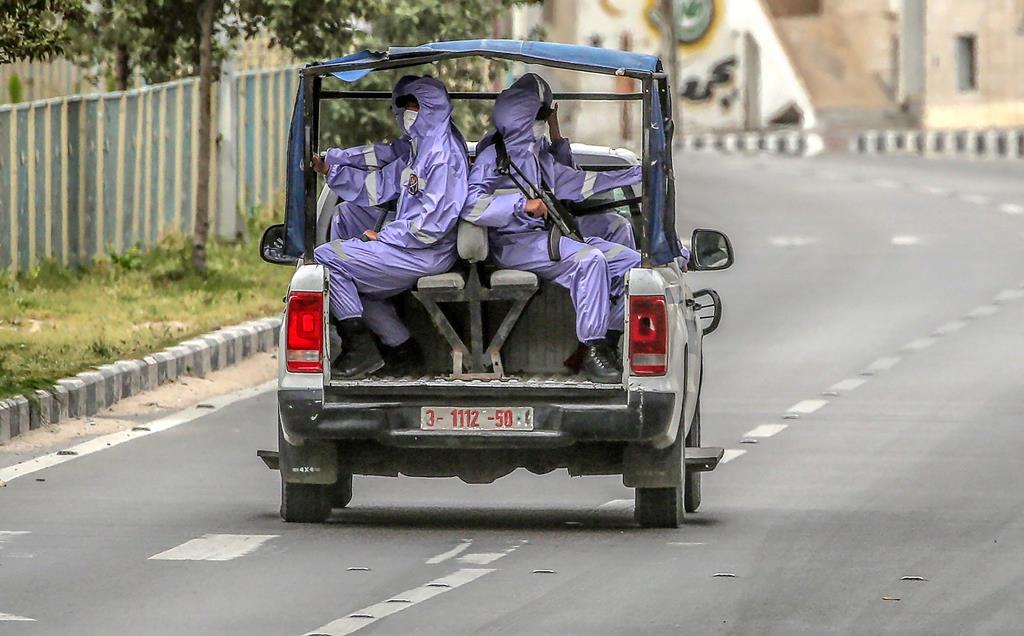 Gaza, Palestina. Agentes de segurança palestinianos vigiam as ruas de Gaza, vestidos com fatos de proteção (06/04/2020). Foto: Mohammed Saber/EPA