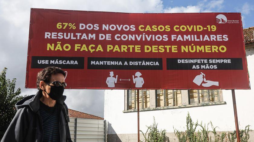 Homem junto a um cartaz, em Paços de Ferreira, que sensibiliza sobre cuidados a ter com covid-19. Foto: José Coelho/Lusa