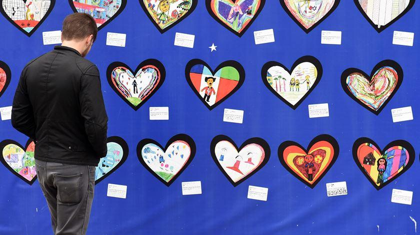 Ler mensagens é também uma forma de homenagear as vítimas. Foto: Neil Hall / EPA