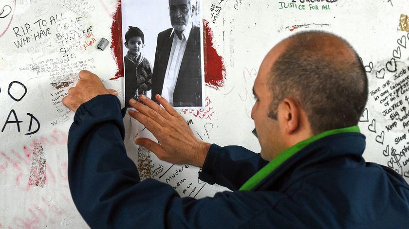 Hamid Ali Jafari coloca uma foto do seu  pai, Ali Yawar Jafari, na  parede de homenagem às vítimas  no  viaduto Westway. Foto: Neil Hall/ EPA