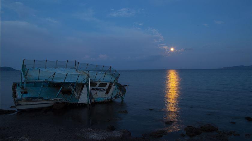 O que resta de um barco de migrantes iluminado pelo eclipse em Sivrice, Turquia, na costa do Mar Egeu. Foto: Tolga Bozoglu/EPA
