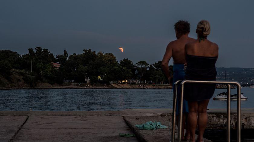 Veraneantes testemunham eclipse em Koper, Eslovénia, junto ao mar Adriático. Foto: Filip Singer/EPA
