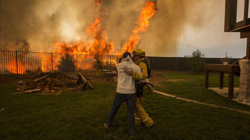 Bombeiro consola homem que tenta proteger casa. Foto: David McNew/EPA