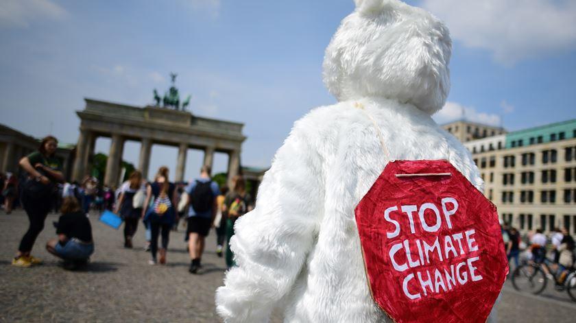 Um jovem vestido de urso polar no protesto junto às portas de Brandenburg, em Berlim, na Alemanha. Foto: Clemens Bilan/EPA