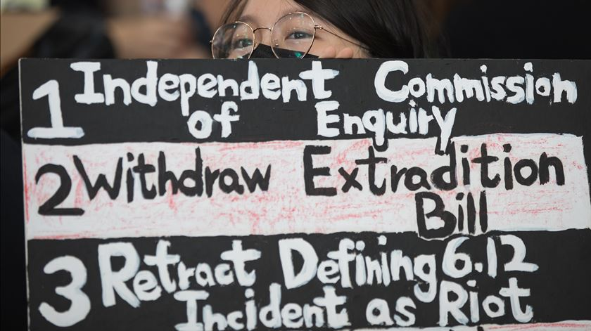 Cartaz exige Comissão Independente de Inquérito e que Governo local não classifique protestos como revoltas. Foto: Jerome Favre/EPA