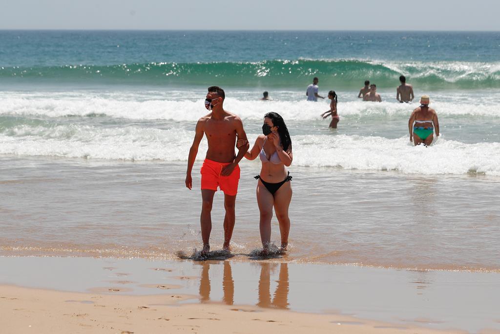 Banhistas com máscara na praia. Foto: António Cotrim/EPA