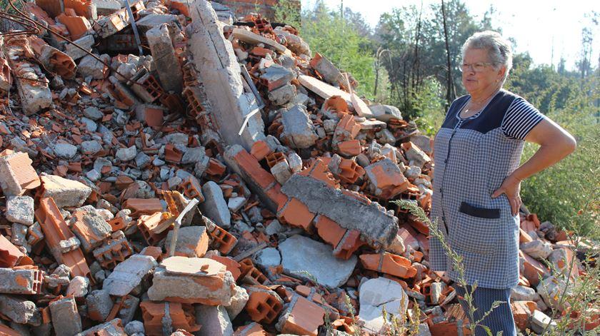 Maria Helena ao lado dos escombros do aviário que ardeu