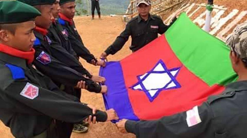 Militantes do Exército Nacional Kuki com a bandeira da organização. Foto: DR
