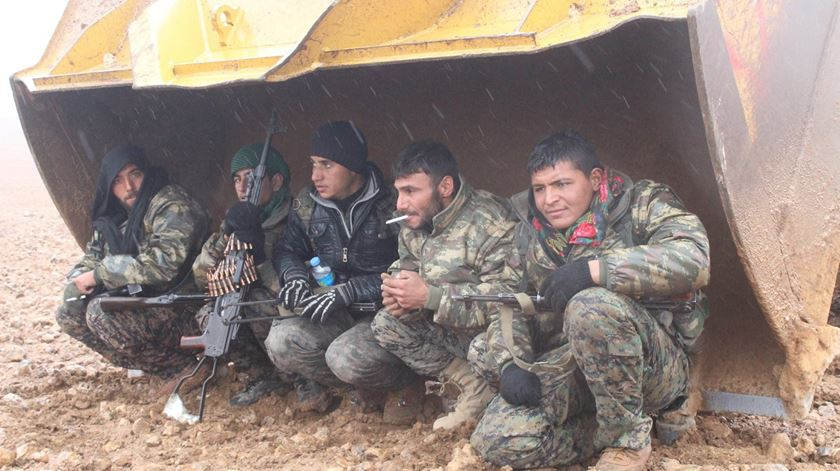 Militares das Forças Democráticas da Síria abrigam-se da chuva durante operações contra o Estado Islâmico. Foto: Facebook YPG
