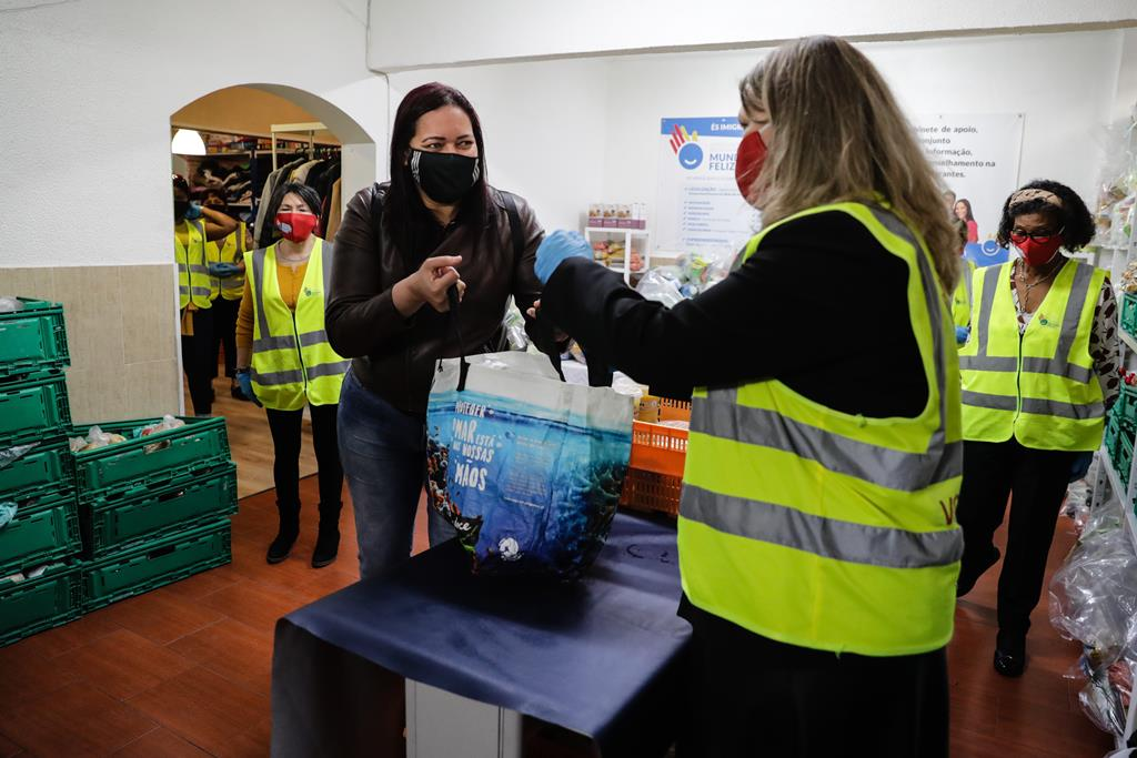 """A presidente da associação """"Mundo Feliz"""", Cecilia Minascurta (2D), enche um cabaz de uma associada, na sede da instituíção de apoio a imigrantes em Algés. Foto: Tiago Petinga/Lusa"""