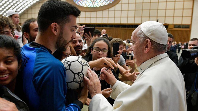 """O Papa Francisco assina uma bola de futebol, num encontro promovido pela """"Gazzetta dello Sport"""". Foto: EPA"""