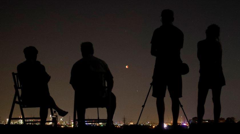 """Curiosos esperam pela chegada da """"lua vermelha"""" de 2018 na cidade de Frankfurt. Foto: Kai Pfaffencach/Reuters."""