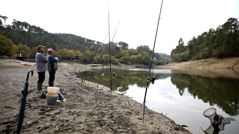 Amadeu e Henrique vêem todos os dias o nível de água na barragem de Fagilde descer. Hoje trouxeram o guarda-chuva porque dizem que a chuva traz o peixe para a superfície da água. Mas não durou muito