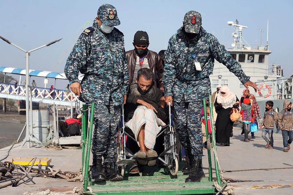 Militares do Bangladesh transportam um idoso de etnia rohingya para o barco que o levará para uma ilha remota. Foto: EPA