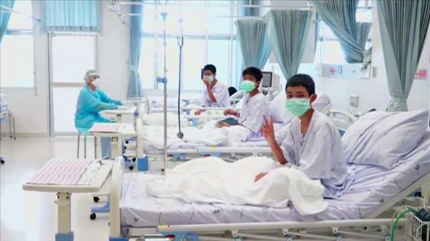 Rapazes tailandeses acenam ao mundo a partir do hospital