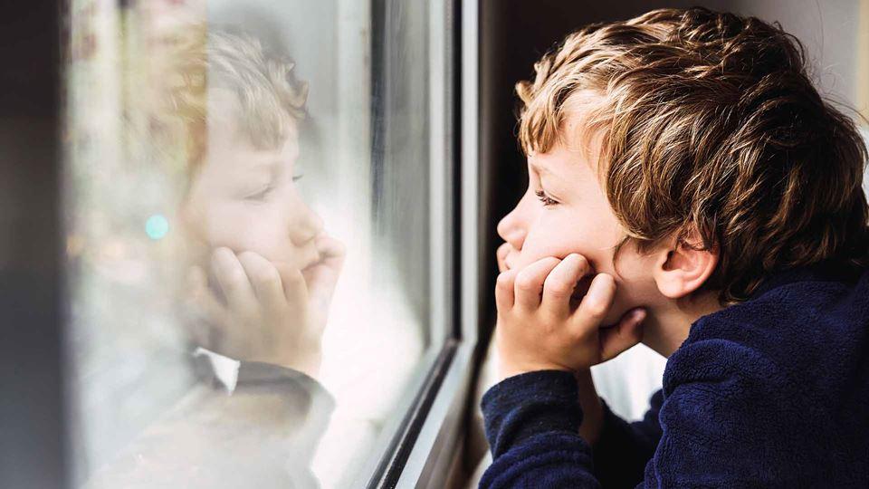 Criança em casa a olhar pela janela