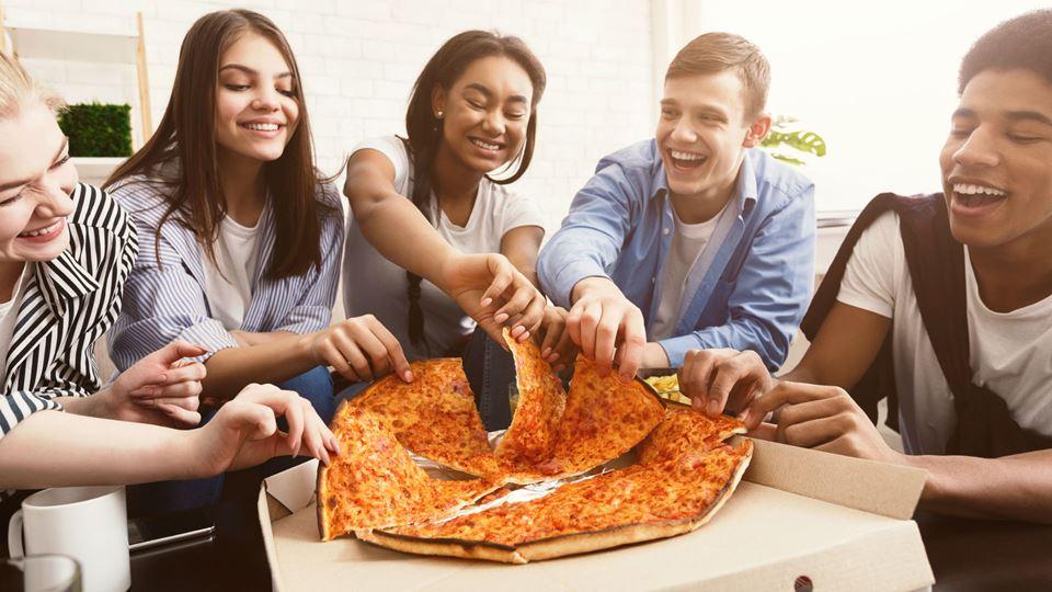 Grupo de amigos a comer pizza
