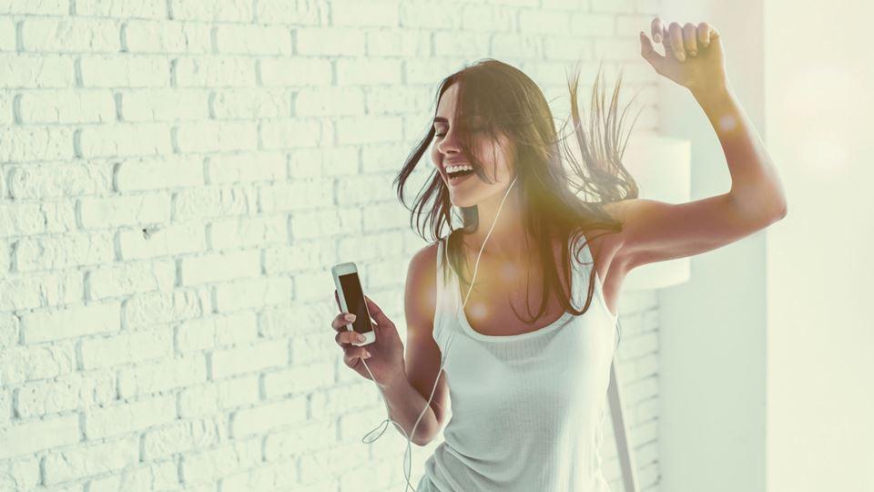 Mulher a cantar e a dançar ao som de música