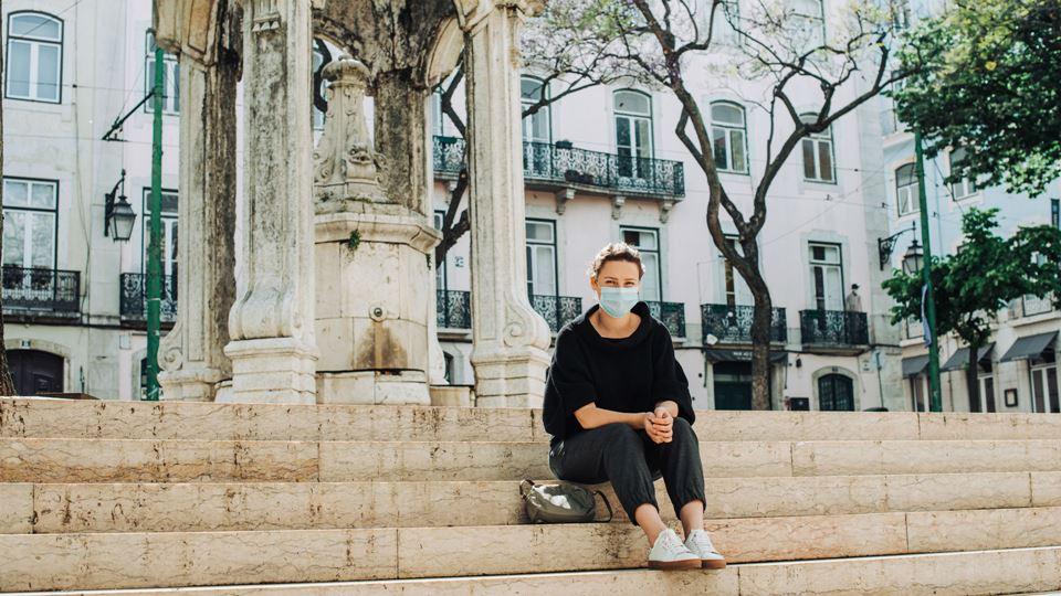 Mulher com máscara sentada