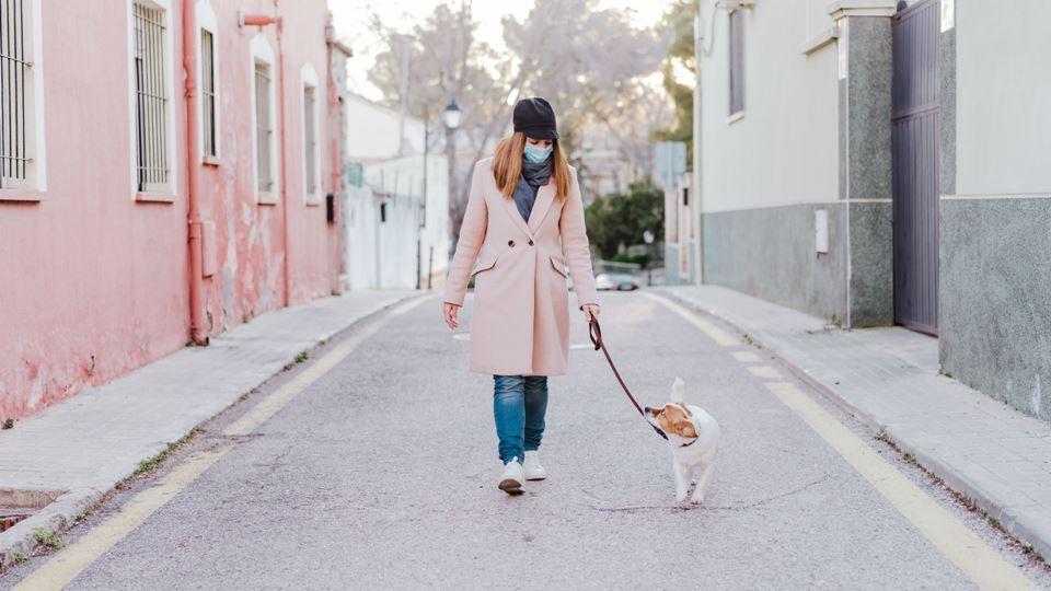 Mulher de máscara a passear cão